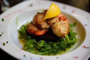 Scallops atop black pudding and greens
